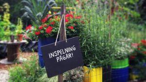 Infoskylt hängandes på staket till trädgård