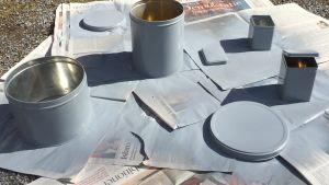 Spraymålade plåtburkar på tidningspapper