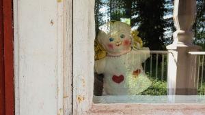 Pieni kankainen mollamaija-nukke puutalon ikkunassa, kuvattuna ulkopuolelta.