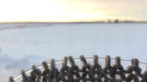 Etualalla lähikuvassa harmaa neuletyö, kaunis talvimaisema taustalla.