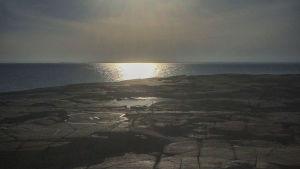 Kalliota, merta, taustalla aurinko paistaa