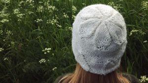 Henkilö, joka kuvattu takaapäin, päässään neulottu myssy.