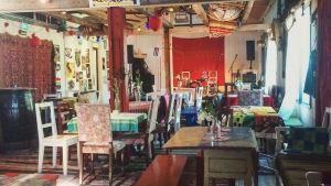 Kahvila, joka sisustettu eripari tuolein ja pöydin, räsymatoin ja värikkäin koristein.