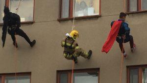 Batman, en brandman och Stålmannen klättrar högt uppe på en husvägg. Någon tittar ut genom fönstret och ser dem.