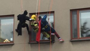 Brandmän utklädda till Batman, brandman och Stålmannen klättrar på en vägg och tittar in genom ett fönster i huset.
