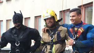 Batman, en brandman och Stålmannen poserar efter att de klättrade på Barnklinikens vägg i Helsingfors inför julen 2015.