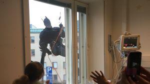 Barn i ett sjukhusrum tittar ut genom fönstret och ser Batman klättra på väggen.