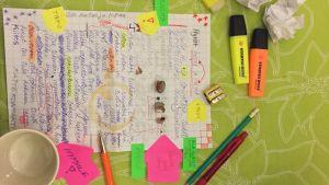 pöydällä muistiinpanovihko ja kyniä