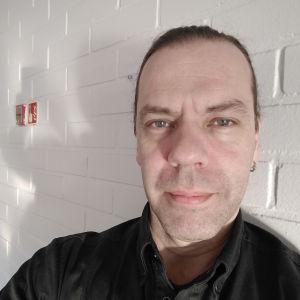 Rolf Granqvist. Selfie mot en vit tegelvägg.