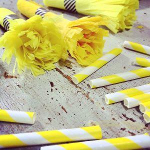 Klippta pappersugrör och gula blommor av creppapper på bord