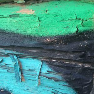 Turkoosi, musta ja vihreä hilseilevämaalinen graffiti tampereella puutalon seinässä v. 2016