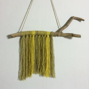Väggbonad med hängande garntrådar från en kvist.