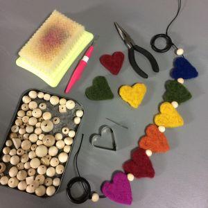 Träkulor, tovade hjärtan och annat material på ett bord