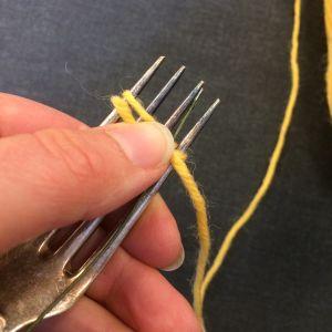 hand som håller i gaffel med gult garn