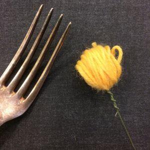 gaffel och järntråd med garnboll i ändan