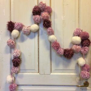 Många garnbollar på ett band, upphängda på en dörr.