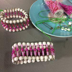 två armband av säkerhetsnålar och pärlor och material till dem på ett bord.