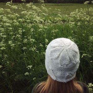 Person sedd bakifrån med stickad mössa på huvudet och grönskande landskap runtomkring