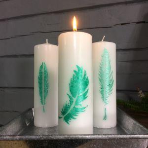 Tre vita blockljus med mönster föreställande gröna fjädrar
