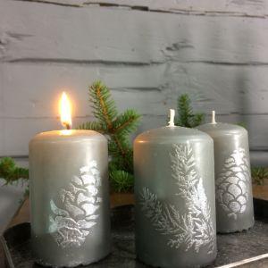 Tre ljusgråa blockljus med mönster föreställande granris och kottar i silverfärg.