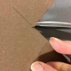 Sormet, paperinahka ja kulma joka leikataan.