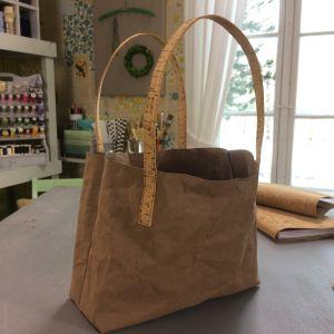 Väska sydd av pappersläder med handtag gjorda av korktyg