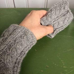 Stickad handledsvärmare på en arm