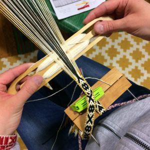 Händer, skyttel med garn och ränning samt del av färdigt vävt band.