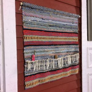 Väggförvaring gjord av en gammal trasmatta upphängd på väggen.