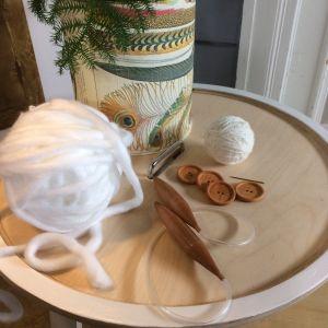 Jumbo garnnystan, tjocka rundstickor, träknappar, nål och garnnystan på ett bord.