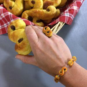 Hand smyckad med ring och armband med lussekatter tar en lussebulle