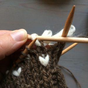 Närbild på stickningen och iläggning av vit ull