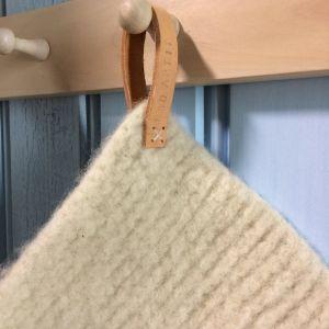 detalj av stickad och tovad grytlapp med läderögla.
