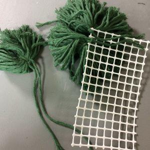 En bit nät på vilken det knutits fast gröna garnbollar