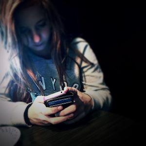 en tonårstjej tittar på sin mobiltelefon i mörkret