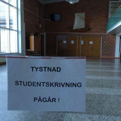 Lapp som uppmanar till tystnad utanför skrivsalen i Pargas svenska gymnasium.