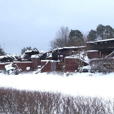Den radhuslänga som förstördes i en brand på Gumnäsvägen i Pojo i januari 2018 är insnöad.