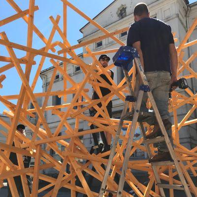 män inne i konstruktion av gula pinnar