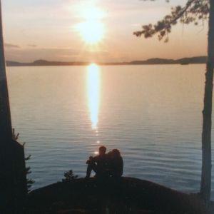 Kaksi ihmishahmoa istuvat kalliolla veden äärellä ihailemassa auringonlaskua.