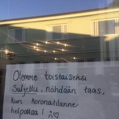 Kahvilan ikkunassa oleva lappu, jossa kerrotaan kahvilan olevan toistaiseksi suljettu koronatilanteen vuoksi.