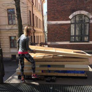 Minna Tervamäki siirtää kulissiseiniä auton lavalla.
