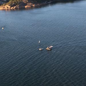 Helikopterbild av en motorbåt har kapsejsat i havet, flera båtar är på plats för att hjälpa.