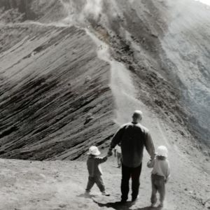 Jussi Pakkasvirta taluttaa kahta pientä tytärtään tulivuoren laella avautuvassa maisemassa.