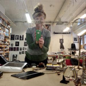 Peilin kautta otettu kuva Ulla Jokisalosta työhuoneellaan, etualalla pöytä takana kirjahylly ja valokuvia seinällä.