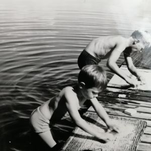 Jussi ja Timo Pakkasvirta pesevät mattoja Kivijärven laiturilla kuumana 1960-luvun kesäpäivänä.
