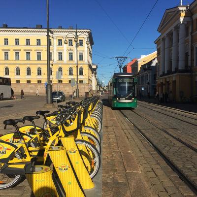 En lång rad av stadens gula lånecyklar i en ställning vid Senatstorget.