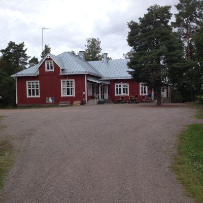 En röd träbyggnad och en vit rappad byggnad som är Västankvarn skola i Ingå.