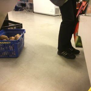 Ett par fötter i svarta joggingskor, matkassar som personen håller i, bakom personen syns en korg med potatis.