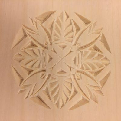 En ljus träskiva som dekorerats med ett runt ornament i träsnitt.