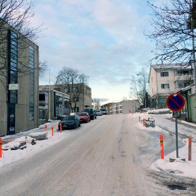 En snöbeklädd väg. Till vänster syns parkerade bilar.